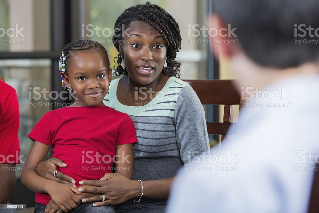 Mother and daughter talking with counselor during family counseling session stock photo