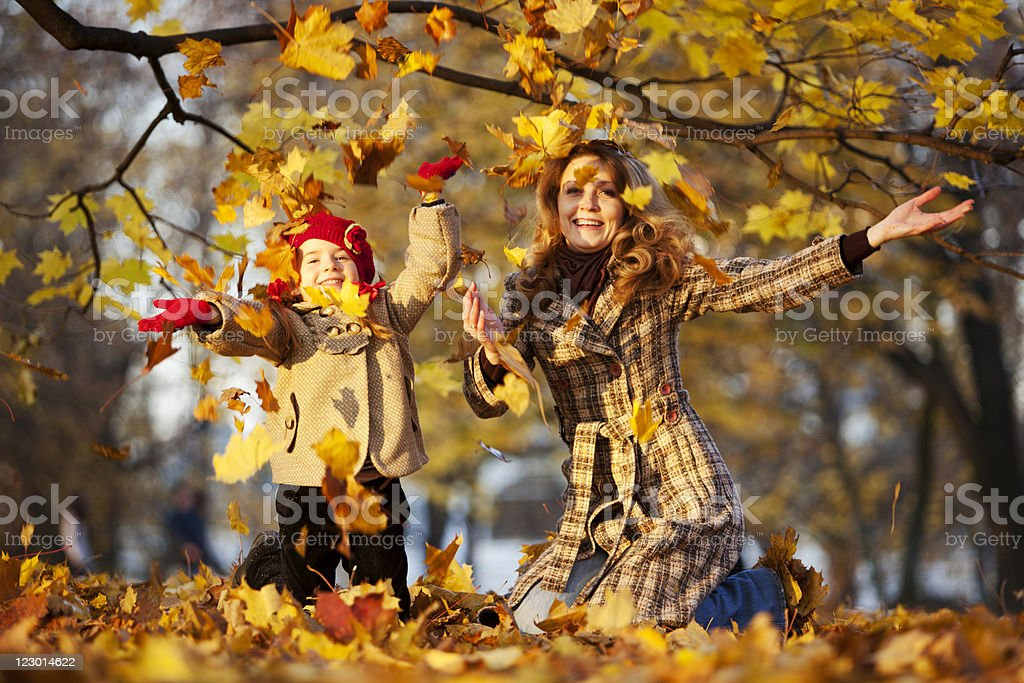 Mother and Daughter Throwing Dry Leaves in Autumn Park royalty-free stock photo