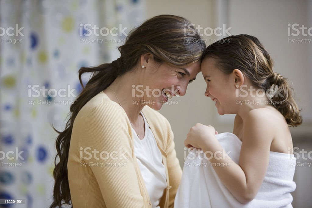 Mother and daughter touching foreheads after bath royalty-free stock photo
