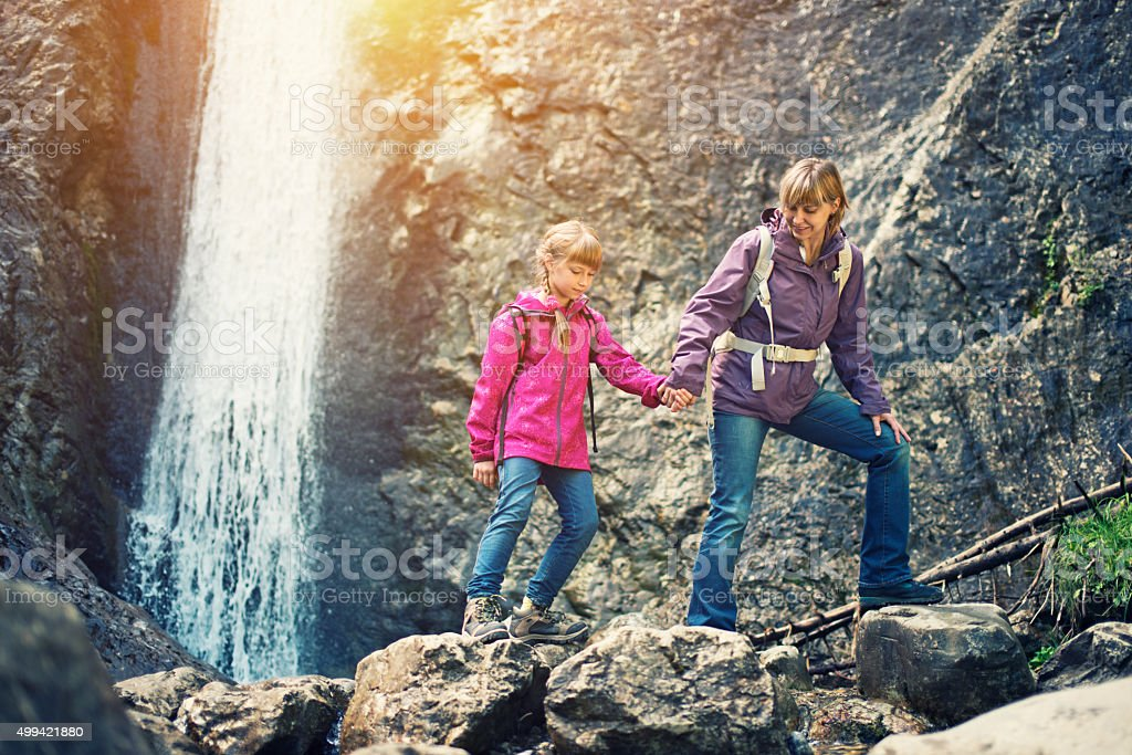 Mother and daughter trekking by the waterfall stock photo