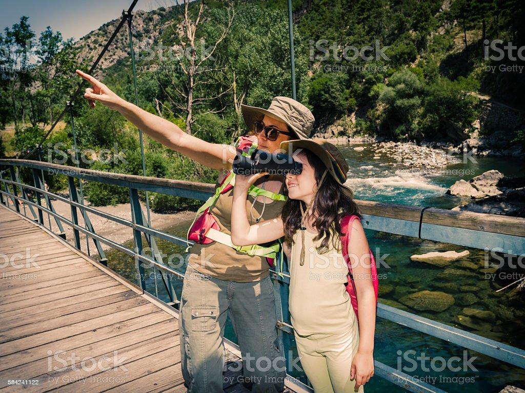 Mother and daughter trekking in nature stock photo