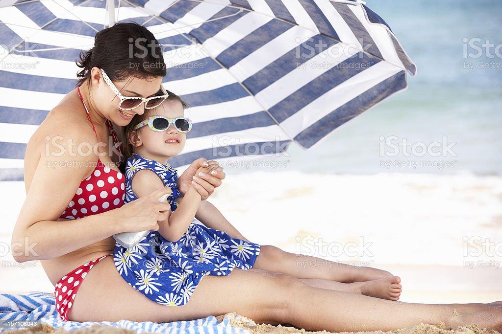 Mother And Daughter Under Beach Umbrella Putting On Sun Cream stock photo