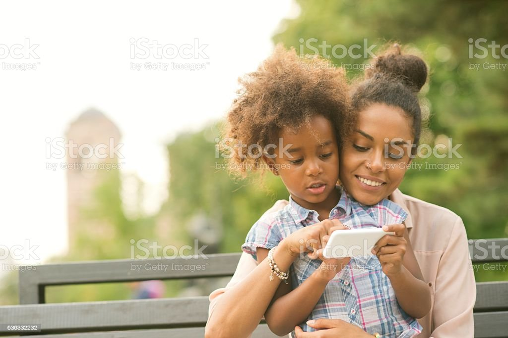 Mother and daughter usin smartphone stock photo