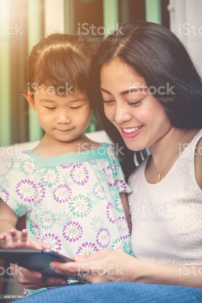 Mother and daughter using digital tablet. Family spending time together. stock photo