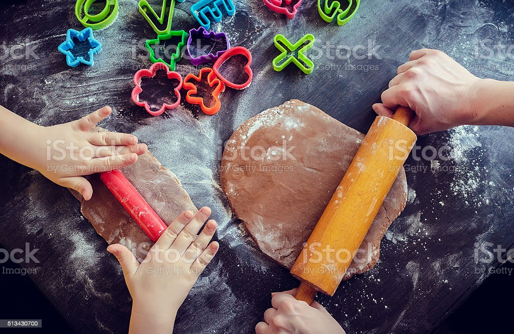 Mother and daughter using rolling pins together in the kitchen stock photo
