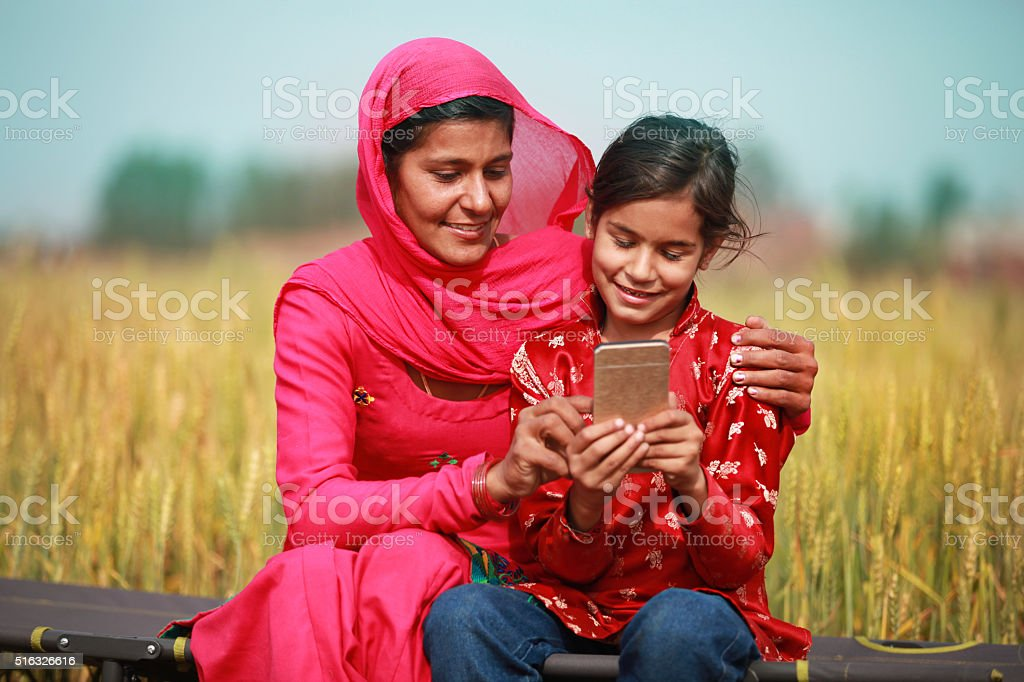 Mother And Daughter Using Smartphone stock photo