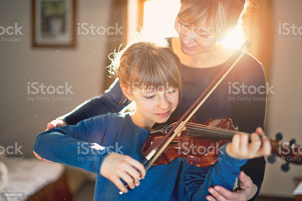 Mother and daughter violin lesson stock photo