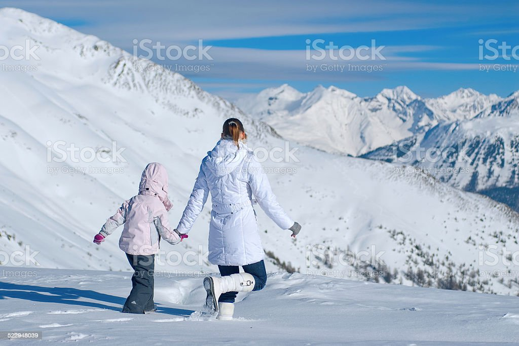 Mother and daughter walking in the mountains of  vast snow stock photo