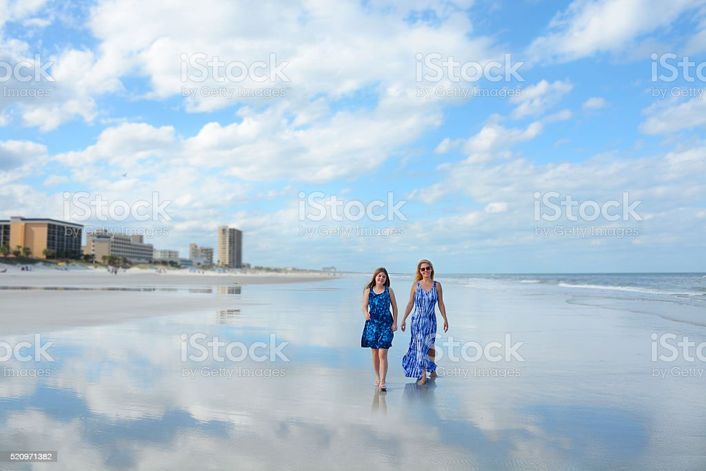 Mother and daughter walking on beautiful beach. stock photo