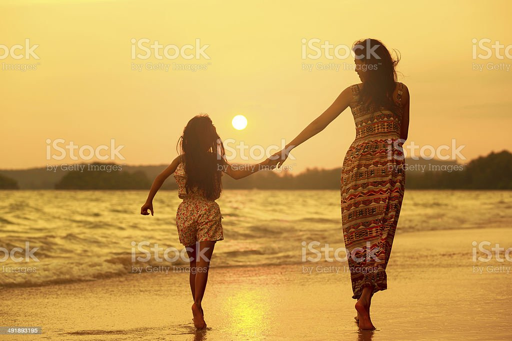 Mother and daughter walking on the beach royalty-free stock photo