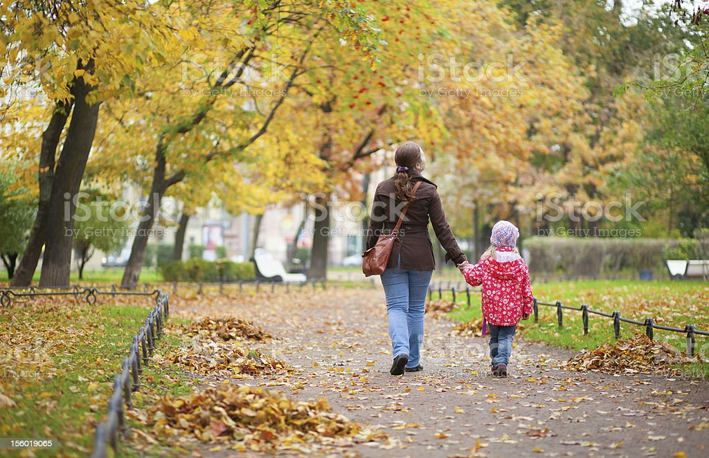 Mother and daughter walking together at beautiful autumn day royalty-free stock photo