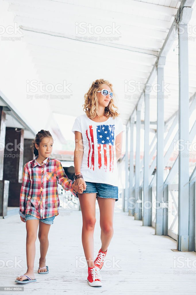 Mother and daughter walking under open shelder and holding hands stock photo