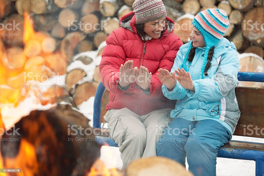 Mother and daughter warming hands by fire stock photo