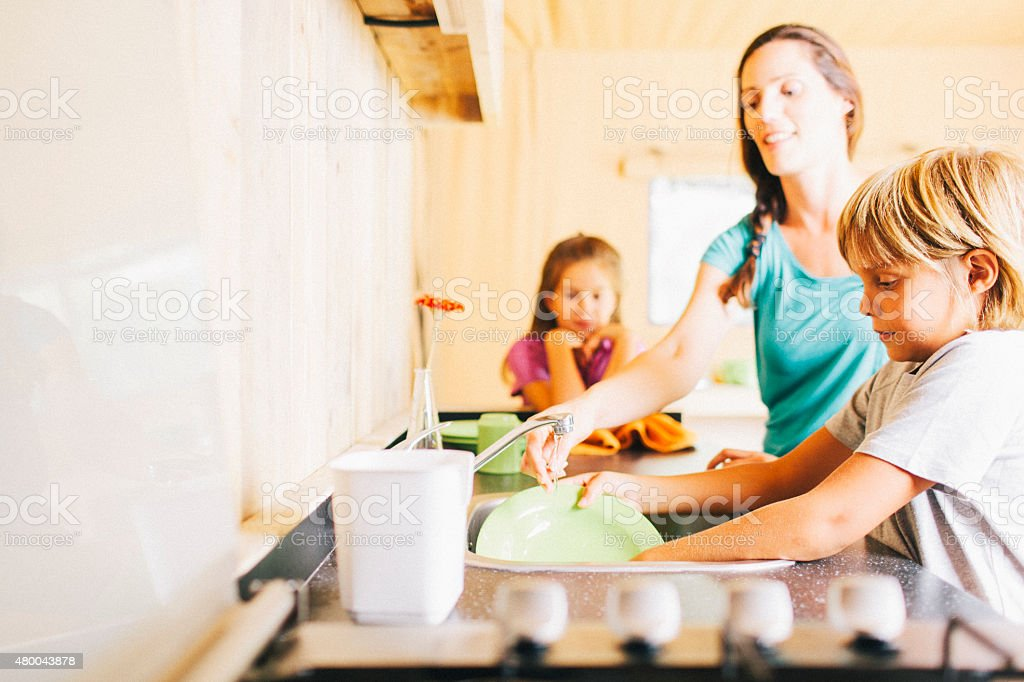 Mother and daughter washing dishes. stock photo