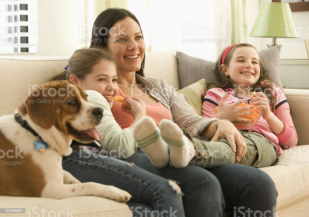 Mother and daughter watch television with family dog royalty-free stock photo