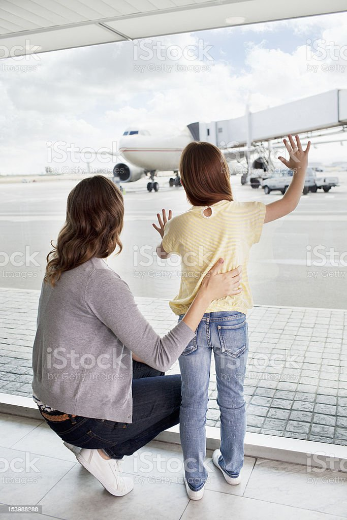 Mother and daughter waving at airplane in airport royalty-free stock photo