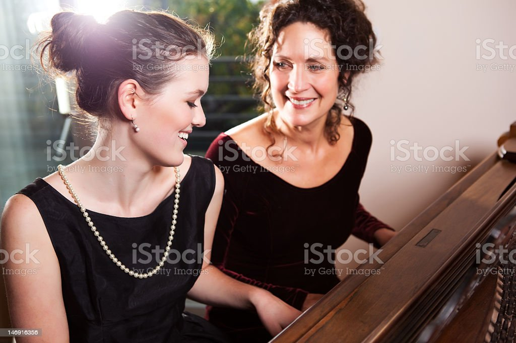 Mother and daughter wearing black playing piano together royalty-free stock photo