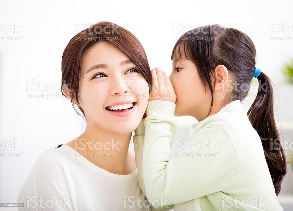 mother and daughter whispering gossip stock photo