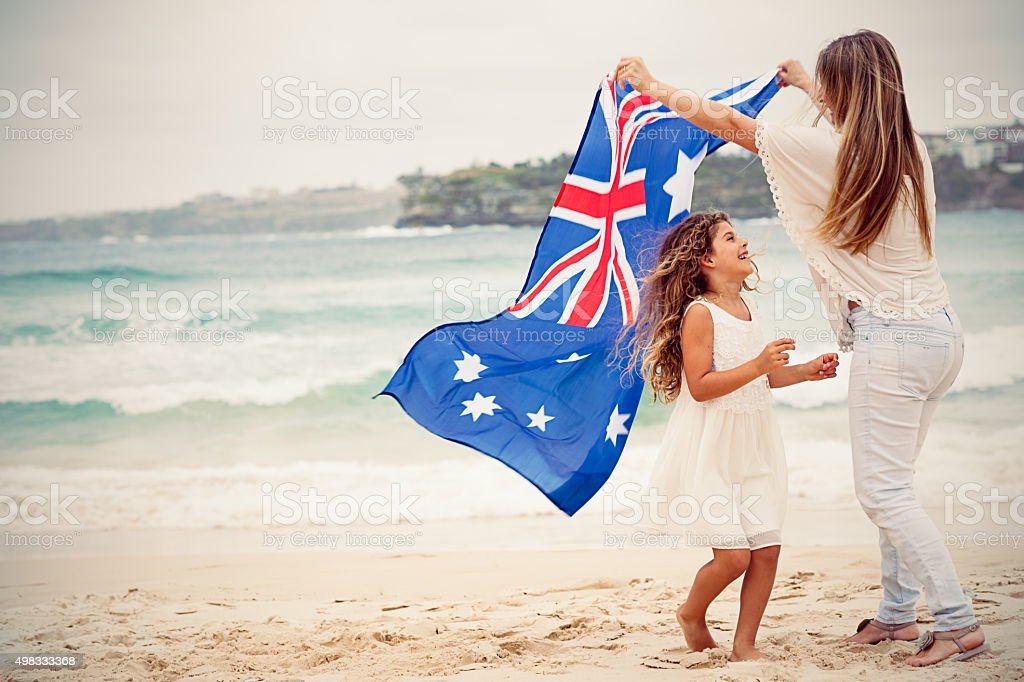 Mother and daughter with Australian flag at the beach stock photo