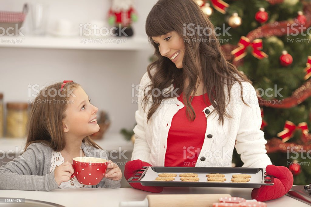 Mother and daughter with cookies by christmas tree. royalty-free stock photo