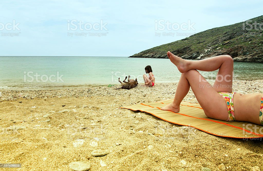Mother and daughter with dog at the beach royalty-free stock photo