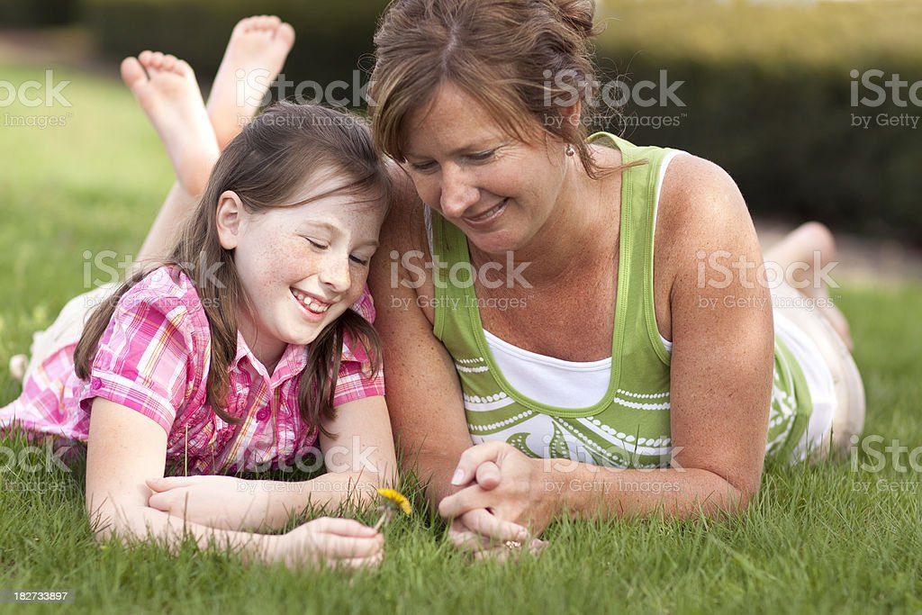 Mother and daughter with flower on grass (Series) royalty-free stock photo