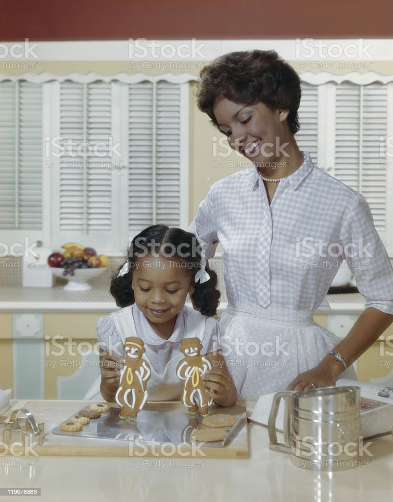Mother and daughter with gingerbread biscuits, smiling stock photo