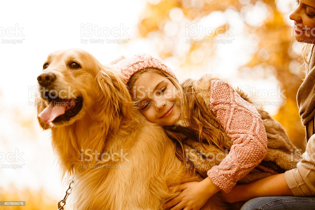Mother and daughter with their dog in autumn park stock photo