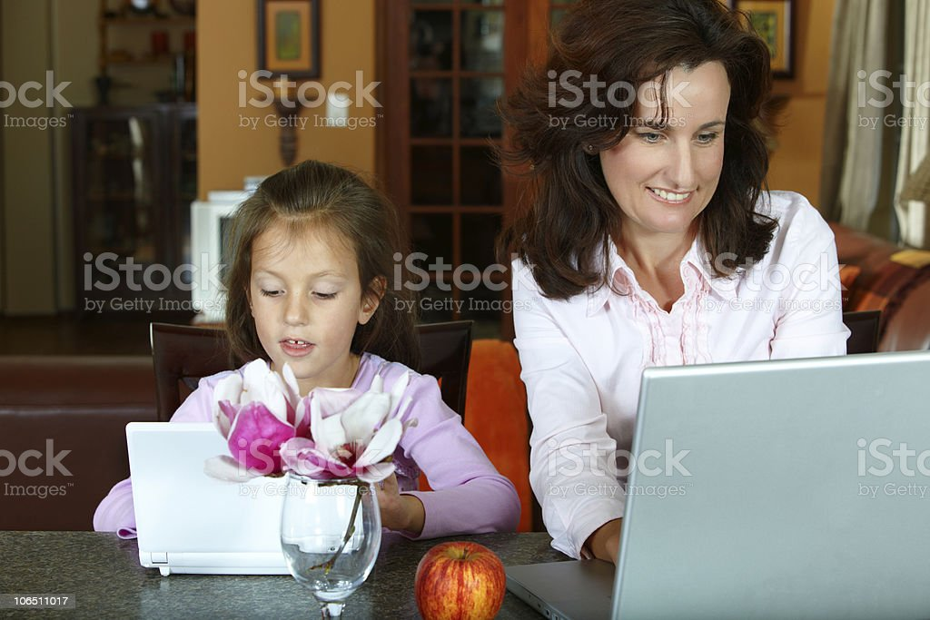 mother and daughter working on laptops royalty-free stock photo