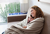 Mother and daughter wrapped in blanket on couch