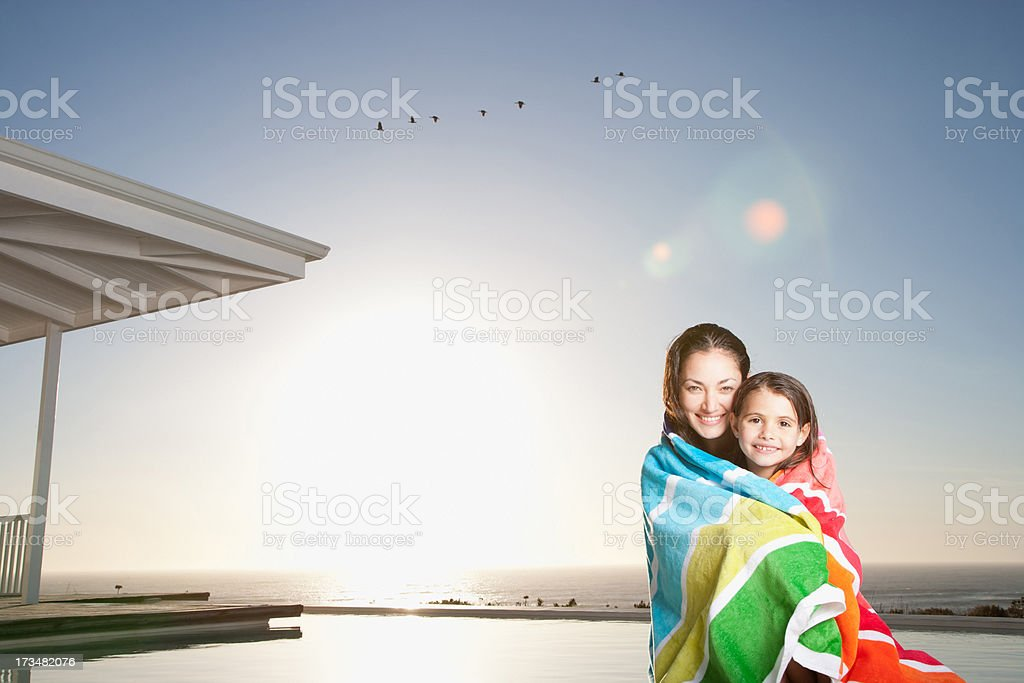 Mother and daughter wrapped in towel poolside stock photo