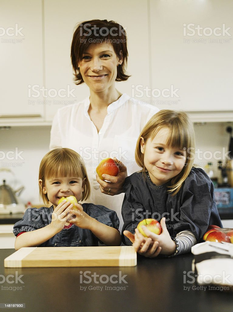 Mother and daughters eating in kitchen royalty-free stock photo