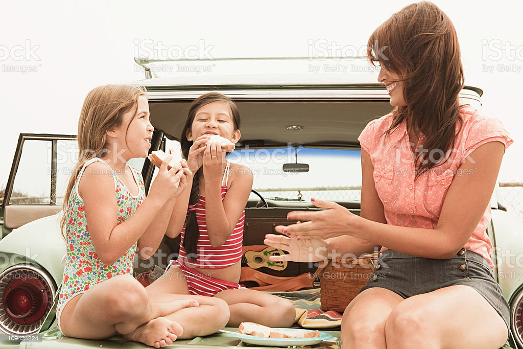 Mother and daughters eating sandwiches on car boot stock photo