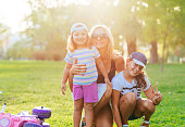 Mother and daughters having fun in park on sunny day