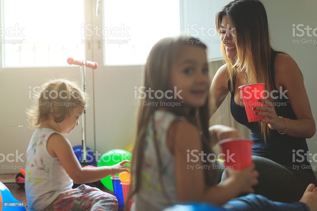 Mother and daughters having fun together at home stock photo