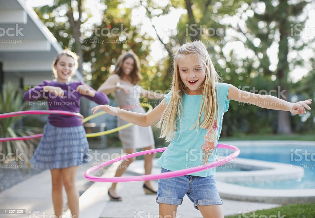 Mother and daughters hula hooping outdoors stock photo