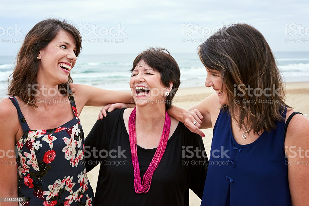 Mother and daughters laughing happily togehter on the beach stock photo