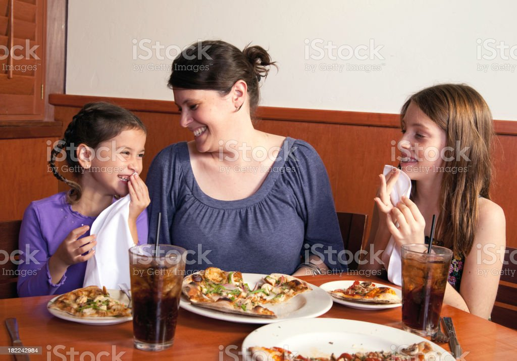 Mother and daughters laughing together while eating pizza royalty-free stock photo
