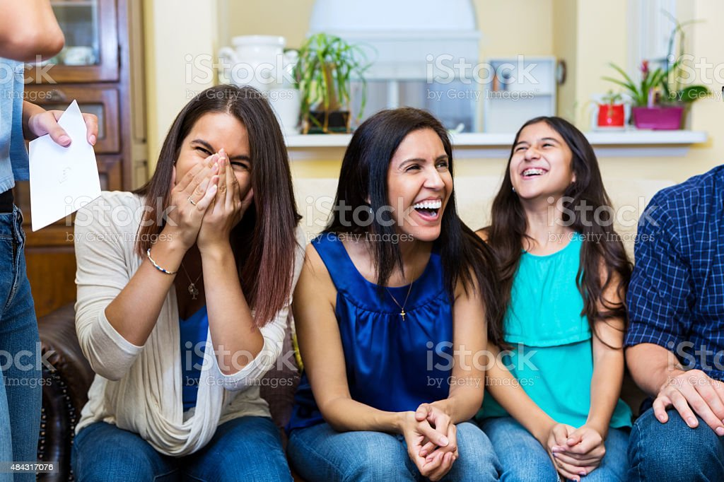 Mother and daughters laughing while spending time together stock photo