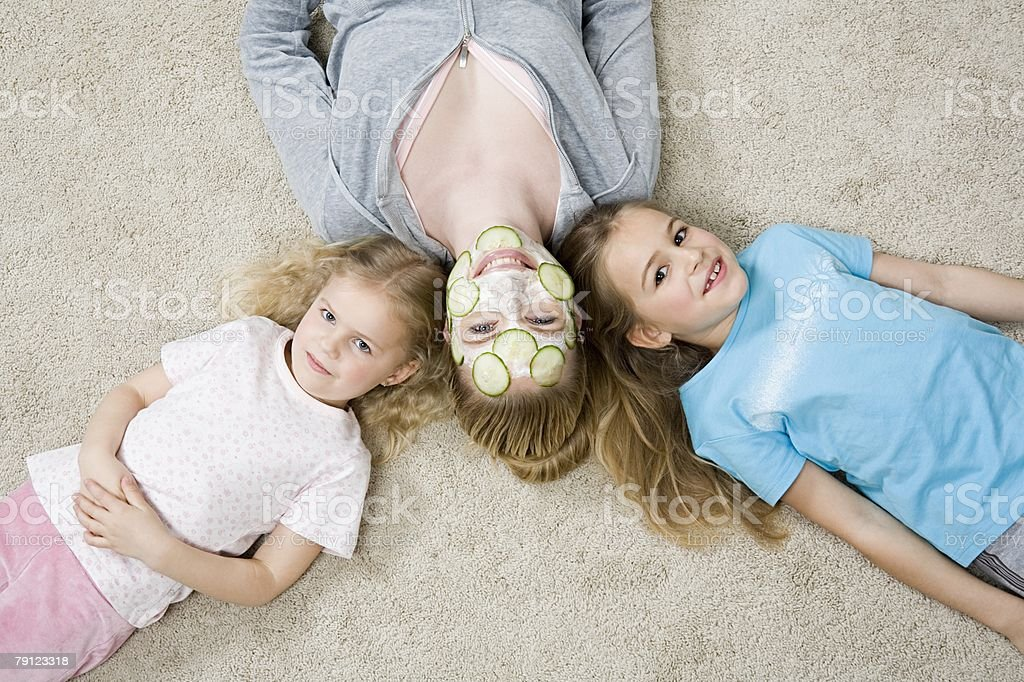 Mother and daughters lying down stock photo