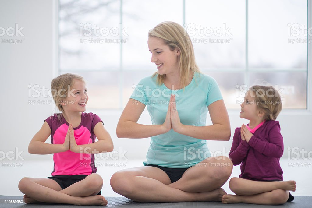 Mother and Daughters Meditating Together stock photo