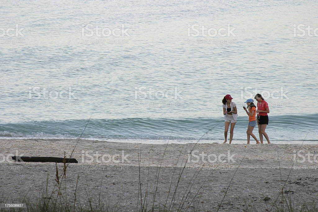 Mother and daughters on the beach stock photo