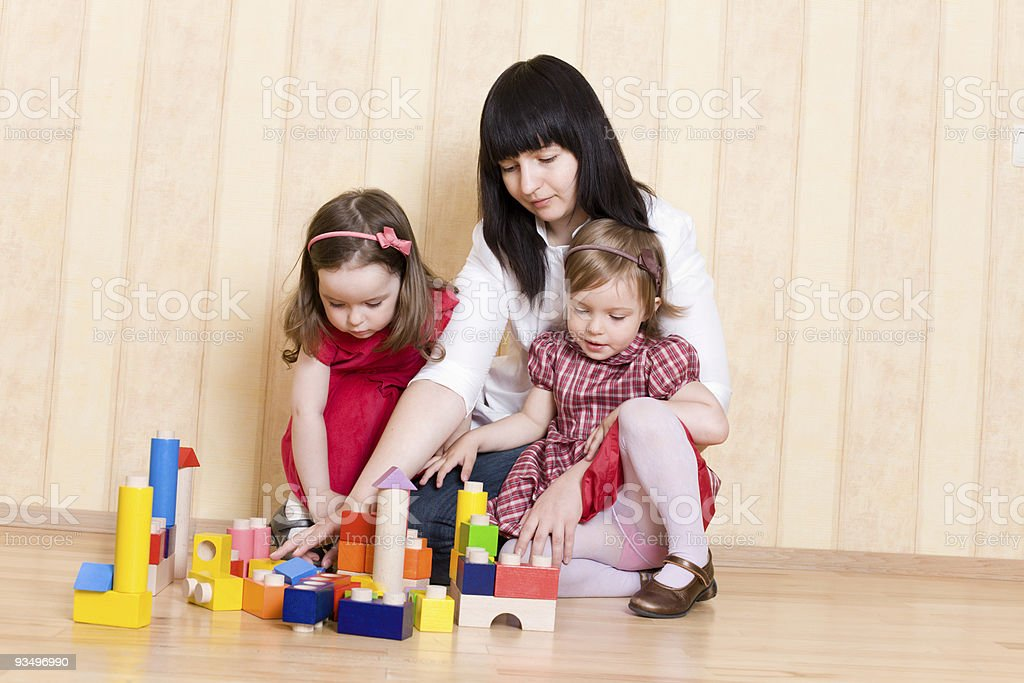 Mother and daughters play with bright geometric toys royalty-free stock photo