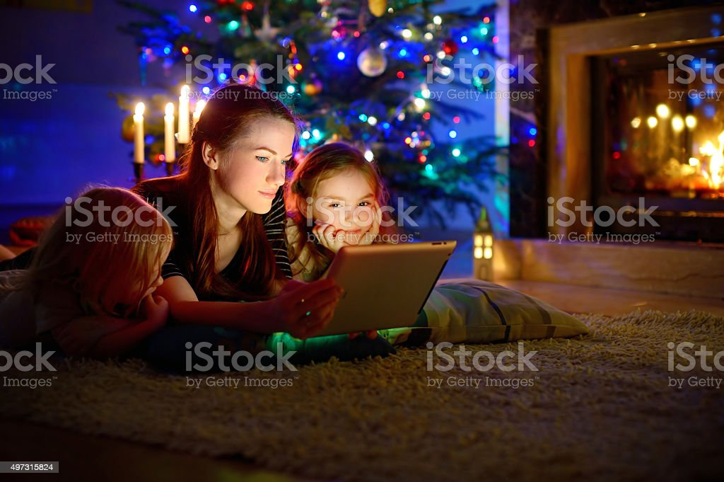 Mother and daughters using tablet by a fireplace on Christmas stock photo