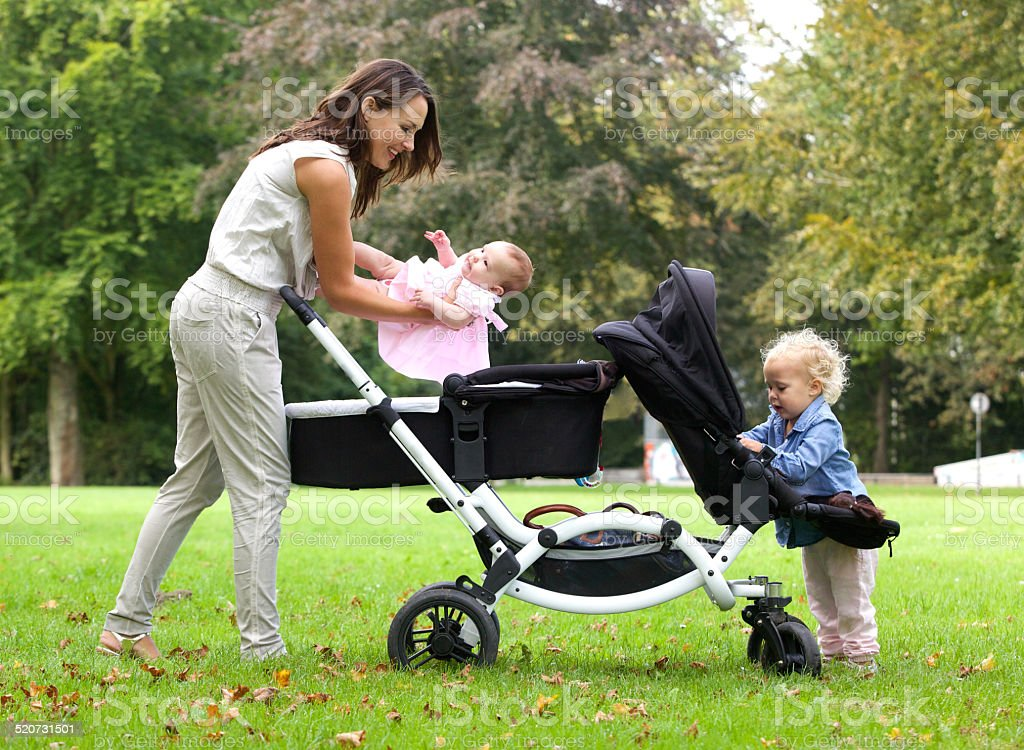 Mother and daughters with pram outdoors stock photo