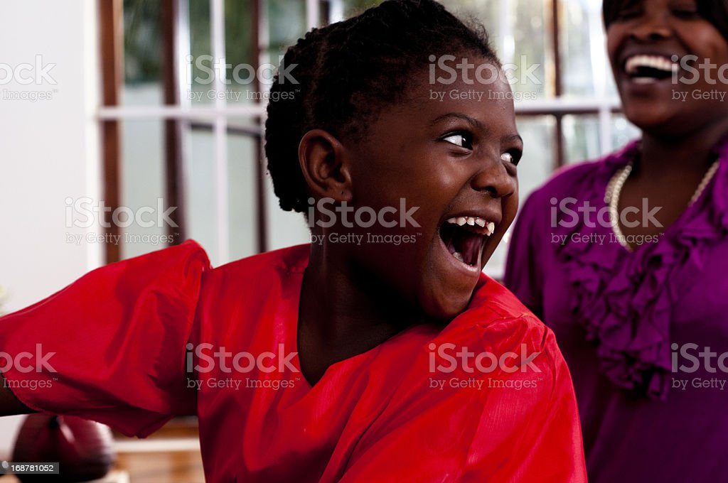 Mother and daugter smiling at each other in kitchen stock photo