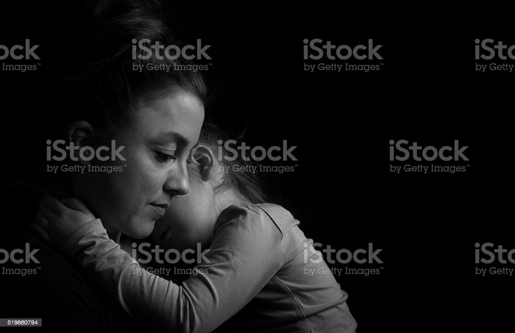 Black and white Picture of a child hugging her mother.Silhuette...