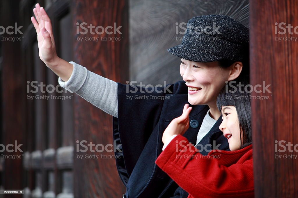 Mother and dauter waving at someone with smile stock photo