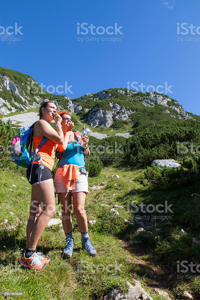 Mother and doughter hikers eating muesli bar stock photo