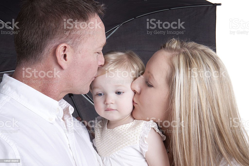 Mother and Father Kissing Baby on Cheek royalty-free stock photo